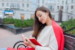有长的棕色头发和白色牙微笑的一个可爱的女孩在都市背景坐长凳并且写她想法  免版税库存照片