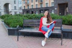有长的棕色头发的一个可爱的女孩在城市背景坐长凳并且写她想法在一个红色笔记本 她佩带 免版税库存照片