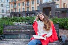 有长的棕色头发的一个可爱的女孩在城市背景坐长凳并且写她想法在一个红色笔记本 她佩带 图库摄影