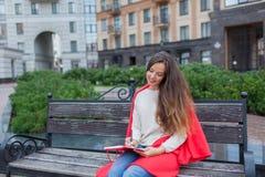 有长的棕色头发的一个可爱的女孩在城市背景坐长凳并且写她想法在一个红色笔记本 她佩带 免版税库存图片