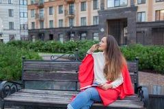 有长的棕色头发的一个可爱的女孩坐长凳,掩藏在一个红色地毯后,咬笔和认为在都市backgroun 免版税库存图片