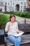 有长的棕色头发的一个美丽的女孩坐与书和尖酸的玻璃的长凳,当读时 她离开了房子  库存照片