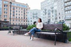 有长的棕色头发的一个美丽的女孩坐与书和尖酸的玻璃的长凳,当读时 她离开了房子  免版税图库摄影