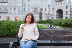 有长的棕色头发的一个美丽的女孩坐与书和尖酸的玻璃的长凳,当读时 她离开了房子  库存图片