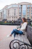 有长的棕色头发的一个美丽的女孩坐与书和尖酸的玻璃的长凳,当读时 她离开了房子  免版税库存图片