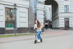有长的棕色头发的一个年轻和可爱的女孩在乘坐在新的住宅复合体的一件轻的毛线衣一辆滑行车 免版税库存图片