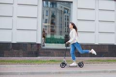 有长的棕色头发的一个年轻和可爱的女孩在乘坐在新的住宅复合体的一件轻的毛线衣一辆滑行车 免版税库存照片