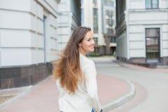 有长的棕色头发的一个年轻和可爱的女孩在乘坐在新的住宅复合体的一件轻的毛线衣一辆滑行车 图库摄影