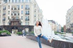 有长的棕色头发的一个年轻和可爱的女孩在乘坐滑行车的一件轻的毛线衣在一新的住宅compl的喷泉附近 免版税库存照片