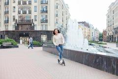 有长的棕色头发的一个年轻和可爱的女孩在乘坐滑行车的一件轻的毛线衣在一新的住宅compl的喷泉附近 库存图片
