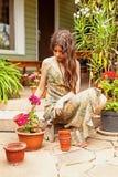 有长的棕色头发的女孩移植在泥罐的大竺葵 库存照片