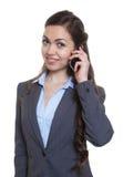 有长的棕色头发的女实业家在电话 库存照片