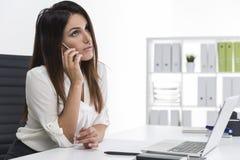 有长的棕色头发的妇女是在电话在一个白色办公室 库存照片