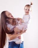 有长的棕色头发的年轻母亲在抱着婴孩的牛仔裤 库存图片