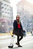 有长的波浪发型的美丽的惊人的深色的妇女在春天或秋天时髦的都市成套装备走在街道上的 启远地街道 库存照片