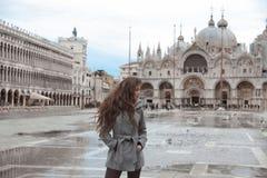 有长的波浪发的美丽的旅游女孩在圣马可广场我 库存照片