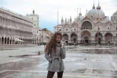 有长的波浪发的美丽的旅游女孩在圣马可广场我 免版税库存图片