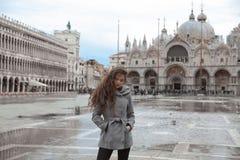 有长的波浪发的美丽的旅游女孩在圣Marco广场我 免版税库存图片
