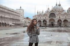 有长的波浪发的美丽的旅游女孩在圣Marco广场我 图库摄影
