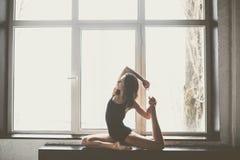 有长的流动的头发的在黑衣裳,泳装美丽的女孩舞蹈家,在一个美好的美好的姿势在大窗口白天, 免版税库存照片