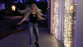 有长的流动的头发的少妇在黄灯夜之前点燃的旅馆` s窗口附近跳舞室外 股票视频