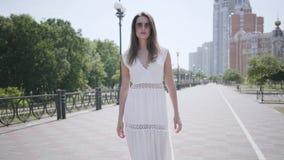 有长的深色的头发佩带的太阳镜和一件长的白色夏天时尚礼服的走画象可爱的少女下来 股票视频