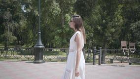 有长的深色的头发佩带的太阳镜和一件长的白色夏天时尚礼服的逗人喜爱的少女步行沿着向下街道的 影视素材