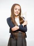 有长的深色的头发的逗人喜爱的微笑的女小学生 免版税库存照片