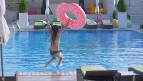 有长的湿头发的亭亭玉立的女孩在有可膨胀的圆环奔跑和跃迁的泳装到在暑假度假村的水池里 股票视频