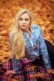 有长的白发的女孩在秋天森林里 免版税库存照片