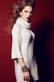 有长的白肤金发的卷发的性感的夫人穿典雅的舒适礼服 免版税库存图片