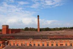 有长的砖烟囱的工厂反对蓝天 免版税图库摄影
