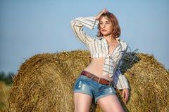 有长的稀薄的腿和赤裸腹部的美丽的女孩在牛仔布短缺和在黄色领域性感的近的干草堆的衬衣 库存照片