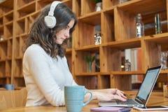 有长的红色卷发的少妇女孩坐在与集中于他们的事务的膝上型计算机和耳机的一张桌上 库存图片