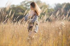 有长的红色吹的头发的秀丽女孩户外 库存图片