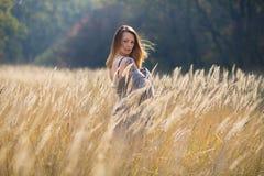 有长的红色吹的头发的秀丽女孩户外 免版税图库摄影