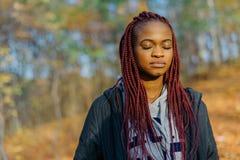 有长的红色头发和闭合的眼睛的美丽的非洲妇女 特写镜头纵向 秋天公园地点 免版税库存照片