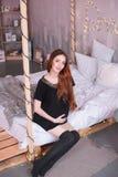 有长的红色头发的孕妇,在一件黑礼服 免版税库存照片