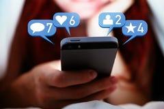 有长的红色头发的少妇使用有表明喜欢、文章、朋友和评论的社会媒介泡影的一个智能手机 库存照片