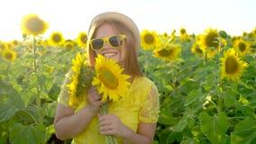 有长的红色头发的秀丽女孩在黄色向日葵领域站立 愉快的户外妇女 青少年 少年 表面 画象 股票录像