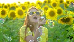 有长的红色头发的秀丽女孩在黄色向日葵领域ang吹的泡影站立 愉快的户外妇女 青少年 股票录像