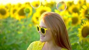 有长的红色头发的秀丽女孩在黄色向日葵领域ang吹的泡影站立 愉快的户外妇女 青少年 影视素材