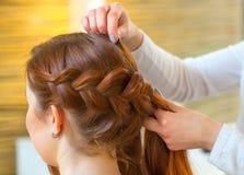 有长的红色头发的美丽的女孩,美发师编织一条辫子,在美容院 免版税库存图片