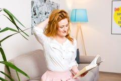有长的红色头发的美丽的少妇学生在桃红色裙子和衬衣阅读书,藏品手中课本坐沙发hom 库存图片