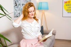 有长的红色头发的美丽的少妇学生在桃红色裙子和衬衣阅读书,藏品手中课本坐沙发hom 库存照片