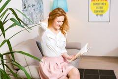有长的红色头发的美丽的少妇学生在桃红色裙子和衬衣阅读书,藏品手中课本坐沙发hom 免版税库存照片