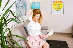 有长的红色头发的美丽的少妇学生在桃红色裙子和衬衣阅读书,藏品手中课本坐沙发hom 免版税图库摄影