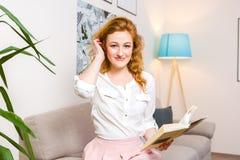有长的红色头发的美丽的少妇学生在桃红色裙子和衬衣阅读书,藏品手中课本坐沙发hom 免版税库存图片