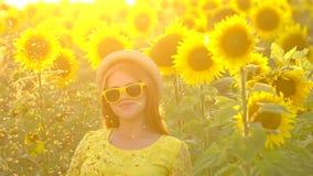 有长的红色头发立场的秀丽女孩在黄色向日葵领域ang洒金子闪烁 愉快的户外妇女 青少年 影视素材