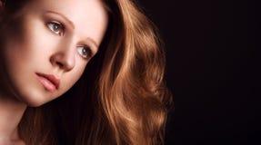 有长的红色头发的哀伤,忧郁女孩在黑暗的背景 库存图片